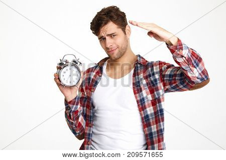 Portrait of a young attractive man holding alarm clock and pointing isolated over white background