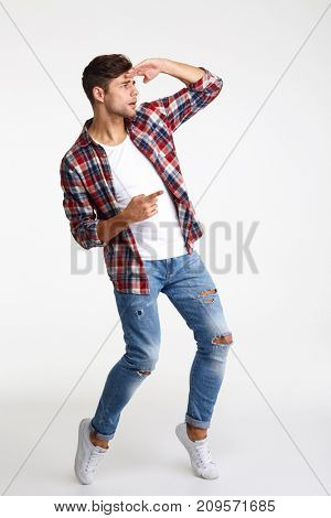 Full length portrait of an attractive man pointing finger away at copy space isolated over white background