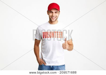 Portrait of a joyful young man in volunteer t-shirt showing thumbs up gesture and looking at camera isolated over white background