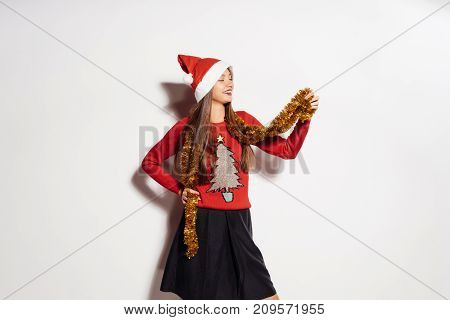 A girl in a New Year hat and a sweet sweater, put on a tinsel. Christmas mood, New Year, Christmas, Santa Claus