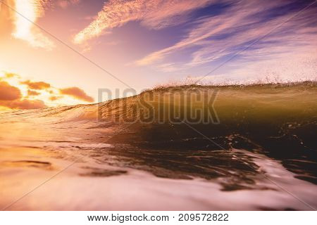 Ocean wave crashing at sunrise. Wave and sun light with cloudy sky