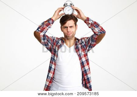 Portrait of a young funny man holding alarm clock on his head and looking at camera isolated over white background