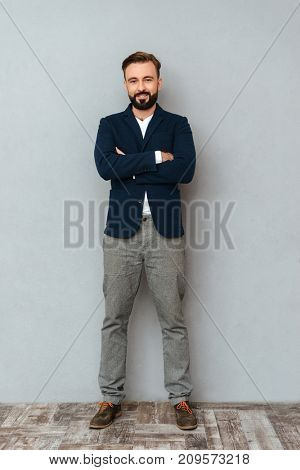 Full length image of smiling bearded man in business clothes posing with crossed arms and looking at the camera over gray background