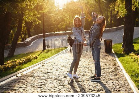 Photo of two cheerful female friends holding hands, showing peace gesture, looking at camera in sunny park