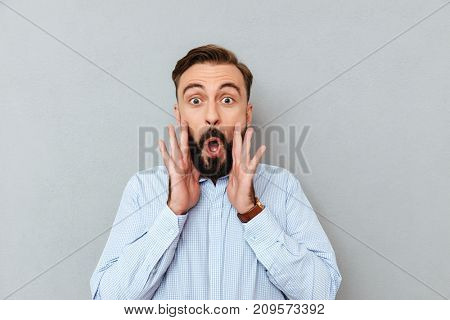 Shocked bearded man in business clothes holding hands near face and looking at the camera over gray background