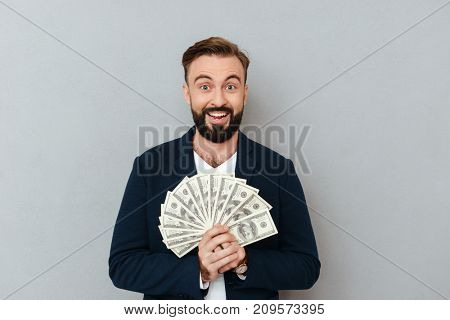 Surprised happy bearded man in business clothes holding money and looking at the camera over gray background
