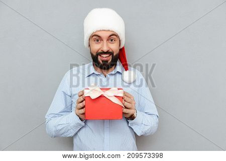 Surprised happy Bearded man in business clothes and christmas hat holding gift and looking at the camera over gray background