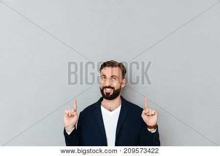 Smiling bearded man in business clothes pointing and looking up over gray background