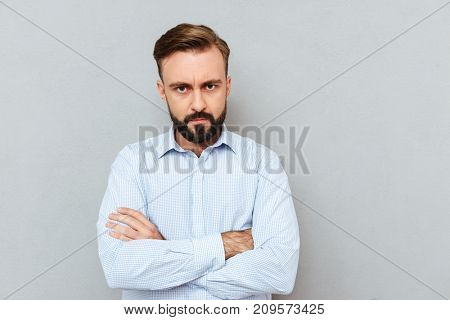 Serious bearded man in business clothes with crossed arms looking at the camera over gray background
