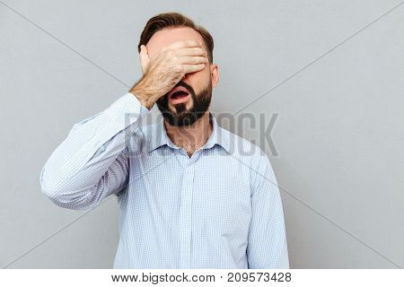 Displeased Bearded man in business clothes covering her eyes over gray background