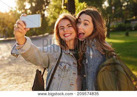 Close-up photo of two funny girls in casual jeans wear making selfie on smartphone, outdoor