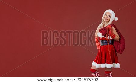 Girl in Santa Claus costume with a bag of gifts on a red background. Christmas. Place for text.