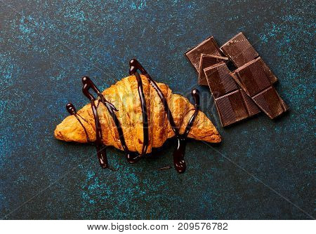 Fresh croissant with chocolate sauce with pieces of chocolate. Bakery product. Copy space for design. Top view.