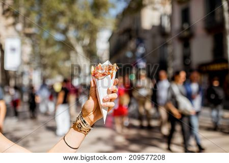 Holding jamon traditional spanish jerked meat outdoors on the street in Barcelona