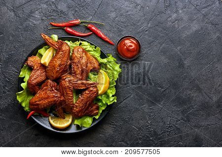 Smoked chicken wings with ketchup and chili hot peppers. Black concrete background. Barbecue. Top view.
