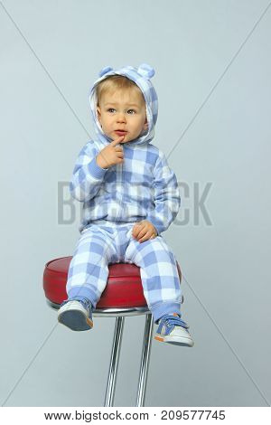 Cute Little Baby Boy Wearing On Sleepwear and Sitting On A Red Chair.