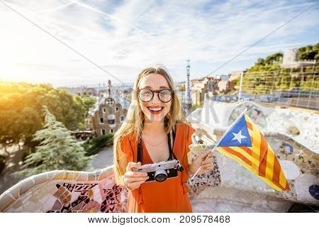 Portrait of a young woman tourist in red dress with catalan flag visiting famous Guell park in Barcelona