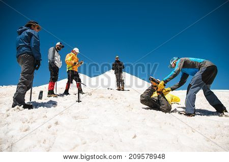 Training to correct slip on a slope or a glacier with the help of an ice ax. A young guide with a beard corrects and helps to learn how to properly slow the slip on the slope with the help of an ice ax. in the background there are observing climbers. Trai