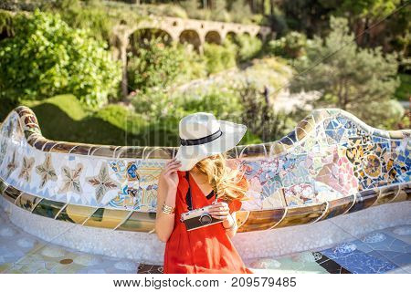 Young woman tourist in red dress sitting on the bench decorated with mosaic in the famous Guell park in Barcelona