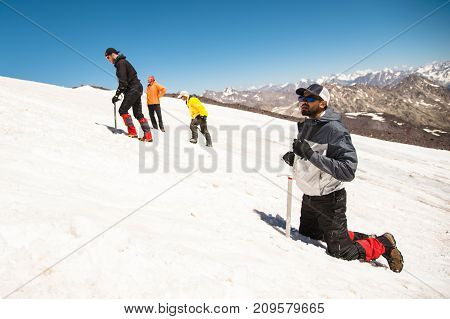 Training to correct slip on a slope or a glacier with the help of an ice ax. A fully equipped backpacker kneels on a snowy slope in the mountains near the ice pick. in the background are watching mountaineers Training an inexperienced climber before climb