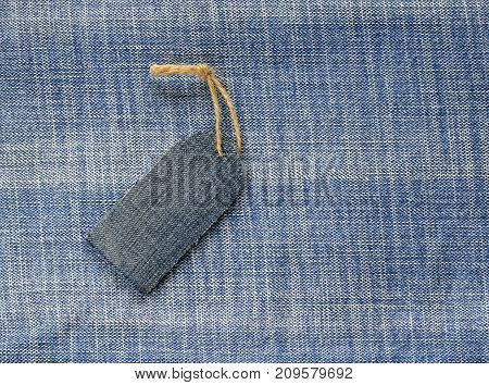 blank price tag on a rope on the background of denim for a seasonal sales