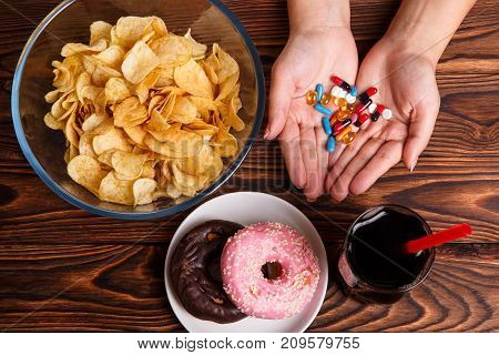 Fast food and drugs. Fast Food with chips, donuts, soda and tablets in hands