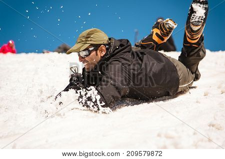 Training to correct slip on a slope or a glacier with the help of an ice ax. A fully equipped backpacker slides on the belly along a snowy slope in the mountains, hindering the glide by an ice ax. Training an inexperienced climber before climbing a mounta