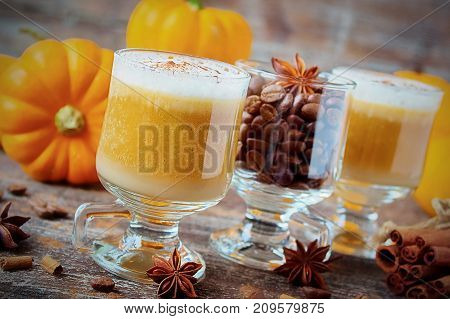 Pumpkin latte with spices and whipped milk foam, a small pumpkin, coffee and cinnamon on old wooden table