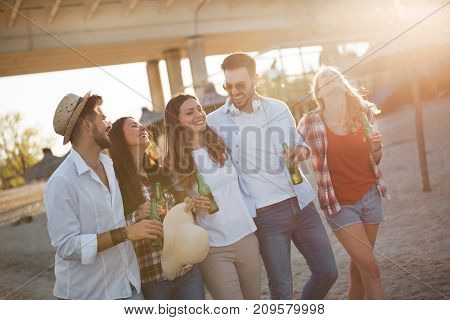 Group of young cheerful friends walking and drinking beer at beach