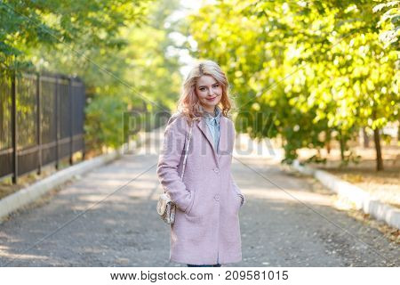 Portrait of a young beautiful girl walking in a stylish attire on a sunny autumn day in a park wearing a pink coat. Everyday lifestyle in the city.