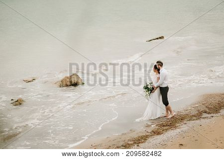 young couple groom with the bride on a sandy beach at a wedding walk