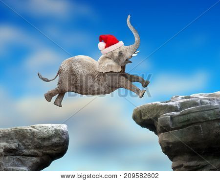 Big Elephant as a Santa jumping over a gap. Successful business metaphor and jump to new year concept.