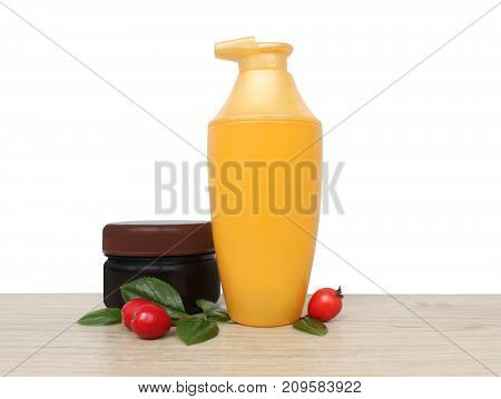 Two jars of cream and berries against a white wall. daily care