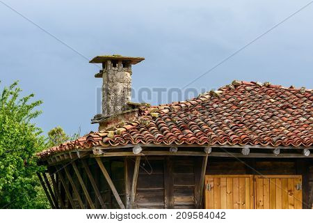 Clay tile roof and chimney made of stone bricks Zheravna village Bulgaria