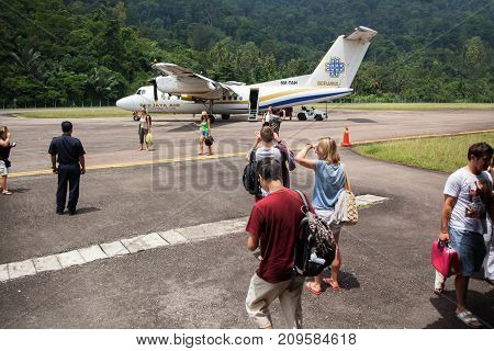 THIOMAN ISLAND MALAYSIA - AUGUST 62012: Tourists go to the plane for their flight through the airfield