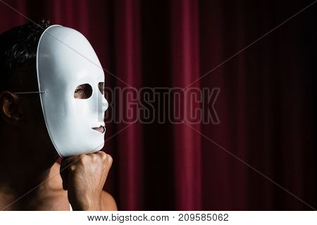 Artist wearing white mask on his face in stage