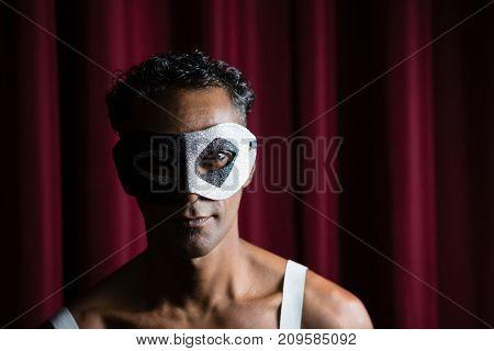 Man wearing masquerade mask in stage
