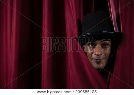 Portrait of ballet dancer peeking through a stage curtain