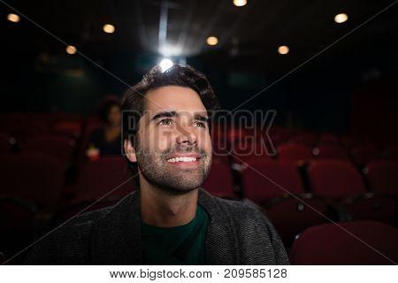 Happy man watching movie in theatre