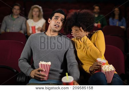 Happy couple watching movie in theatre