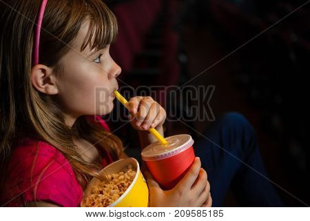 Side view of girl having drink and popcorn while watching movie in theater