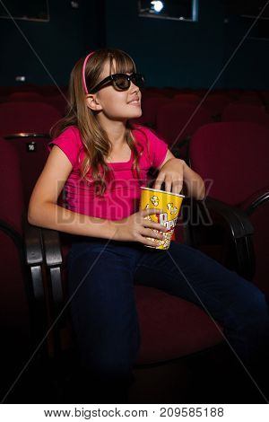 Smiling girl having popcorn while watching movie in theater