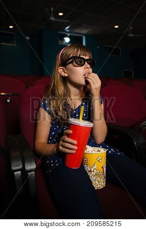 Girl wearing 3D glasses while eating popcorn during movie in theater