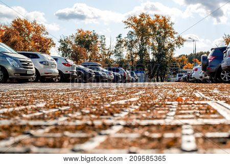 Tourists from different countries parked their cars in the parking lot. Modern cars are perfectly parked. Autumn landscape parking sunny day. Concept of design background for text modern style sunny autumn day.