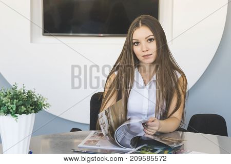the girl in a business suit is sitting at the table leafing through a magazine