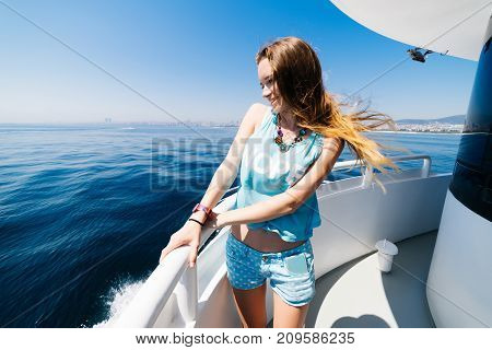Luxury woman smiling on yacht watching on a sea