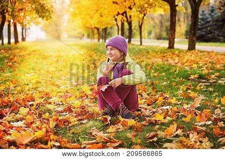 girl in the autumn leaves in the Park in the fresh air, the grass in the sun. bright girl sitting on the grass looking into the distance