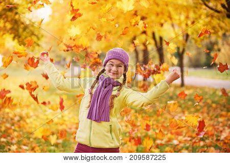 teen girl playing in autumn leaves.A teenage girl spends time with autumn leaves.Bright smile portrait of a child of a teenager with flying maple leaves.