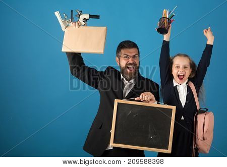 Kid and tutor hold microscope board book and stationery. Education and back to school concept. Teacher and schoolgirl with excited and happy face on blue background copy space. Girl and bearded man