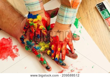 Handprint painting concept. Hands and fingers drawing with multicolor paints on white paper. Arts and crafts. Fathers day family love and care. Imagination creativity and freedom.